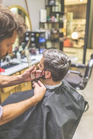 Barbiere che taglia e modella i capelli con forbici e pettine. Archivio Fotografico