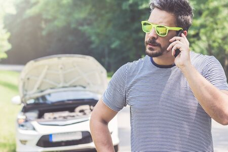 Young modern man making a call with road assistance service by using smartphone. Car with raised hood at the roadside in the background. Stockfoto