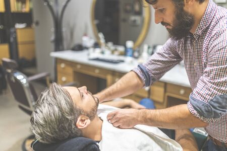 Barber covering client with towel before giving him a shave at barbershop. Stock fotó