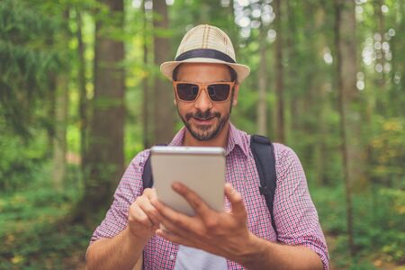 Fashionable man tourist using digital tablet in forest. Banco de Imagens