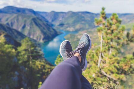 Jambes de randonneur femme avec des chaussures de sport contre la belle vallée et les collines en arrière-plan. Concepts de mode de vie sain et de nature.