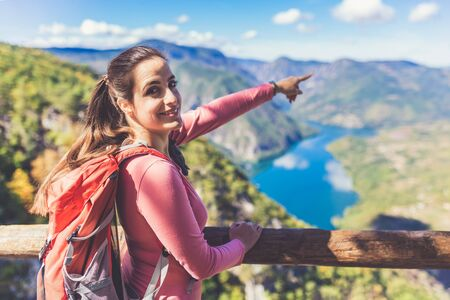 Young female traveler showing beautiful nature while standing on top of the hill. Banco de Imagens