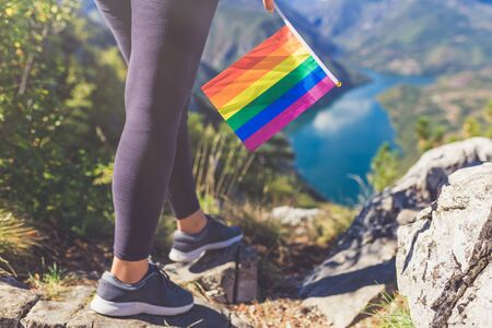 Close up of woman holding colorful rainbow lgbt flag against beautiful nature canyon valley. Freedom concept. Banco de Imagens - 133729680