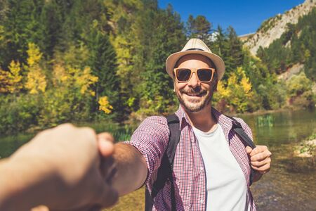 Portrait of fashionable traveler holding woman hand in nature. Travel and love concept. Banco de Imagens
