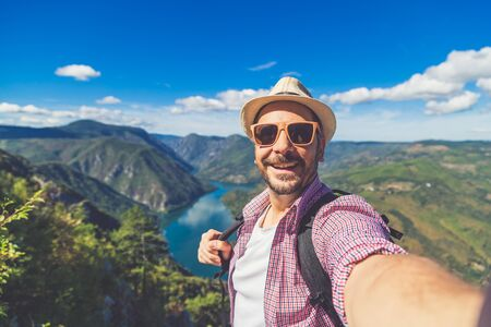 Cheerful man traveler with straw hat and sunglasses taking selfie against beautiful valley. Travel and nature explore concept. Space for copy. Banco de Imagens