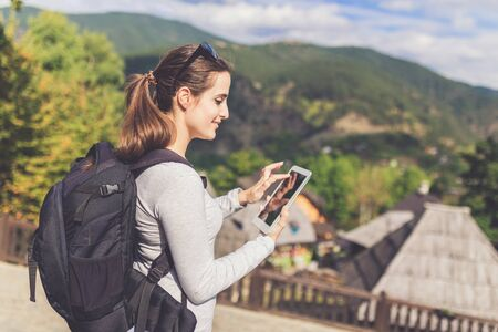 Side view of cheerful beautiful young woman using tablet device near retro mountain village wooden bungalows. Banco de Imagens - 133494025