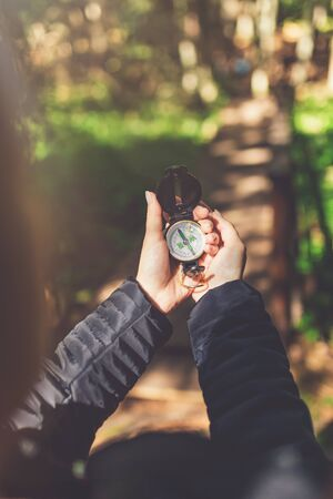 Close up of female hands holding compass against forest footpath. Nature orientation concept.