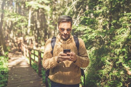 Fashionable man tourist using smartphone while standing on wooden footpath in forest.