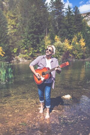 Modern man with acoustic guitar in nature. Banco de Imagens - 133494029