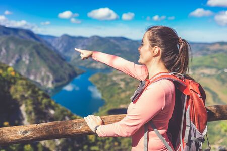 Female hiker or tourist showing beautiful valley in the distance from the top of the mountain. Travel and nature concept.