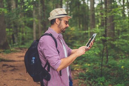 Modern hipster guy holding tablet device in nature. Travel, technology and healthy lifestyle concept. Banco de Imagens - 133494033