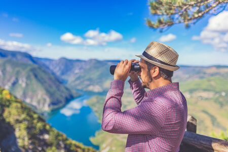 Modern young hipster tourist looking through binoculars while standing on the top of the mountain and enjoying beautiful view of lake or river valley with hills.