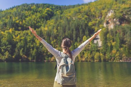 Rear view of young woman wearing backpack with raised arms against beautiful lake and trees landscape. Travel and nature concepts.
