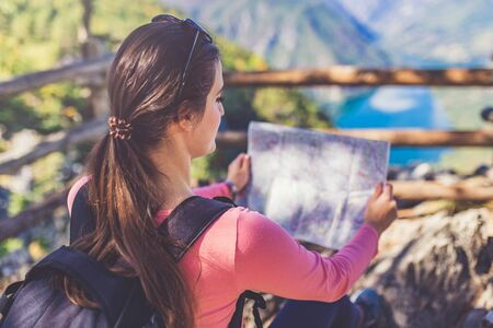 Young traveler holding map and looking at trekking plan on hill above beautiful canyon landscape.