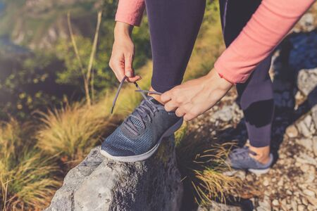 Close up of sportswoman tying shoelace on rock on mountain peak. Active lifestyle and nature concept. Banco de Imagens - 133494035