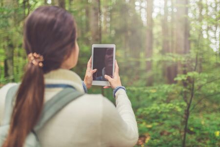 Young female holding blank screen digital tablet device against beautiful forest trees. Nature and technology concept.
