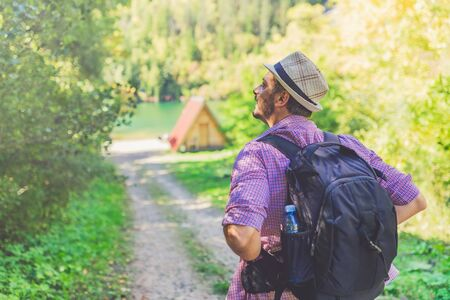 Fashionable tourist with backpack arriving at bungalow on lake coast. Travel and nature concept.