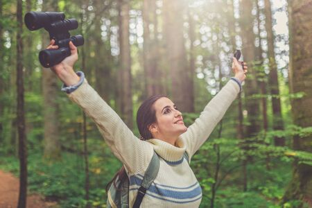 Cheerful young woman with arms raised holding binoculars and compass in forest. Nature and healthy lifestyle concept.