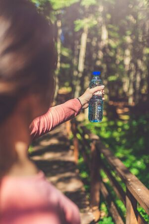 Rear view of young female holding bottle of fresh water in woods or park. Sport and recreation concept. Banco de Imagens