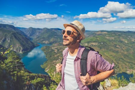Portrait of young tourist on the top of the mountain. Travel and nature concept.