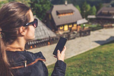 Beautiful young woman using smart phone near retro mountain village wooden bungalows.