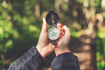 Close up of female hands holding compass against forest footpath. Nature orientation concept. Banco de Imagens - 133493909