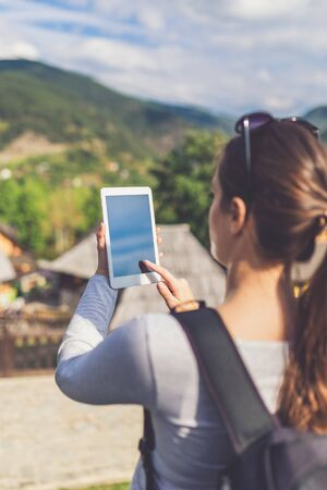 Female tourist holding blank screen digital tablet device against beautiful mountain village. Travel and technology concept. Reklamní fotografie