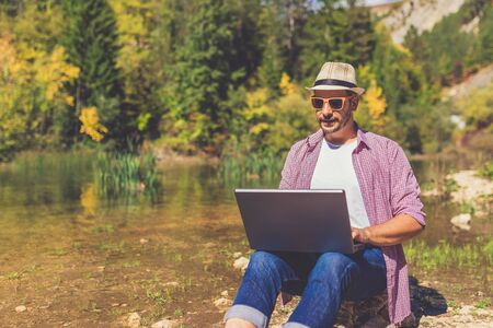 Young fashionable man working on laptop against beautiful nature in the background. Technology and freedom concept. Banco de Imagens - 133493914