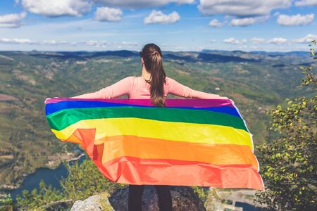 Young woman with lgbt flag enjoying the view from mountain peak. Human rights and freedom concepts.
