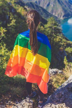 Woman wrapped in rainbow flag against beautiful nature landscape. Banco de Imagens
