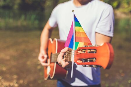 Close up of guitarist playing acoustic guitar with lgbt rainbow flag in nature. Music and freedom concepts.