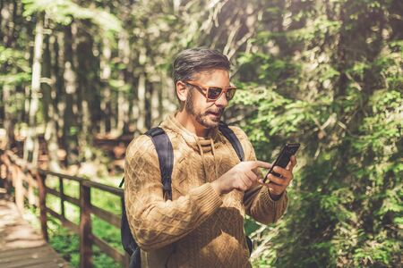 Modern hipster guy holding mobile phone in nature. Travel, technology and healthy lifestyle concept. Banco de Imagens - 133493924