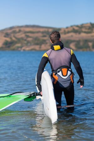 Detail of wind surfer holding board and sail while preparing for the ride.