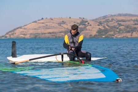 Young man preparing for windsurfing. Banco de Imagens - 133081591