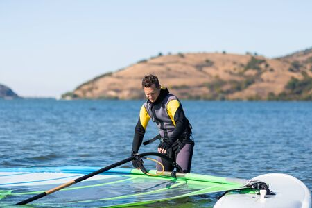 Windsurfer checking his sail and board equipment.