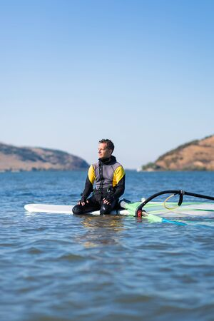 Professional windsurfer wearing wetsuit sitting on board and waiting for wind.