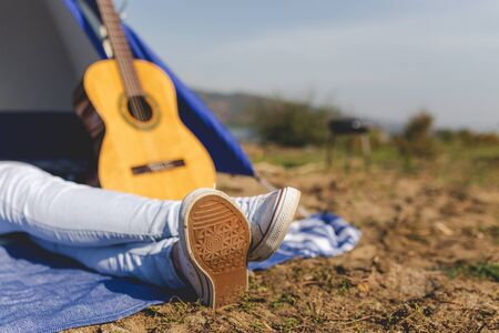 Young female enjoying on camping against acoustic guitar and tent in the background. Space for copy.