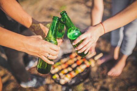 Close up of hands holding beer bottles and cheering over barbecue grill. Food preparation on camping or picnic concept.