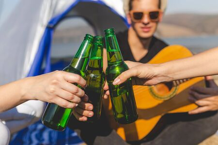 Friends clinking bottles of beer on beach camping picnic. Banco de Imagens - 133493933