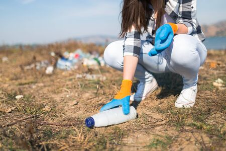 Close up of woman collecting plastic garbage bottle from the ground. Recycling and ecology concept. Banco de Imagens - 133729685