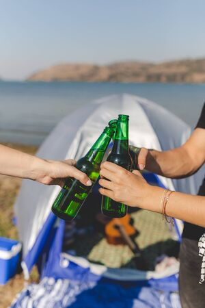Friends clinking bottles of beer on beach camping picnic.
