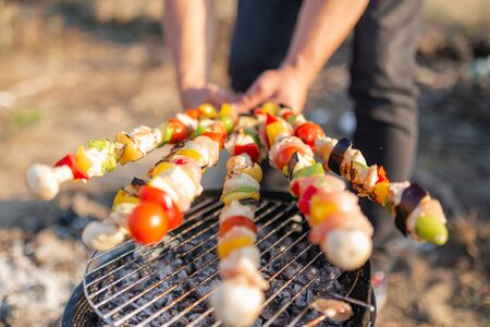 Man hand turning meat and vegetables while grilling on barbecue. Picnic or camping food concept. Banco de Imagens - 133162719