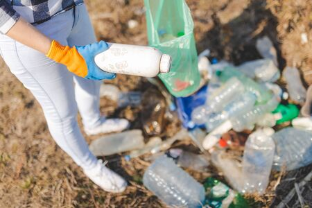 Female volunteer picking up plastic trash outdoors. Environment and save the earth concept. Banco de Imagens - 133729686