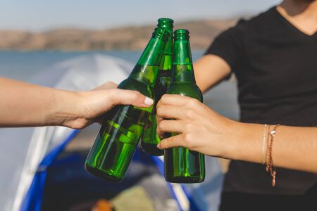 Close up of hands holding beer and cheering against camping tent at the beach. Banco de Imagens - 133162460