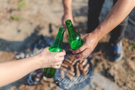 Close up of hands holding beer bottles and cheering over barbecue grill. Food preparation on camping or picnic concept. Banco de Imagens - 133162847