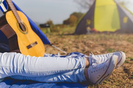 Close up of woman feet lying in front of tent next to acoustic guitar. Freedom and lifestyle concept.