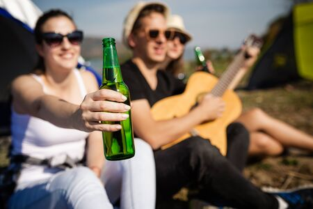 Close up of young female holding beer bottle while having a great time with her friends during camping at the beach. Banco de Imagens