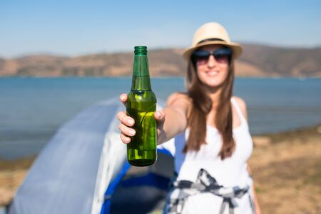 Young woman holding beer bottle in front of camping tent at the coast. Freedom and nature concept. Banco de Imagens - 133493793