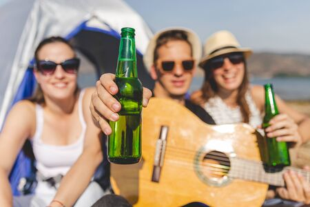 Guitar player showing bottle of beer while having a great time with his friends during camping at the beach.