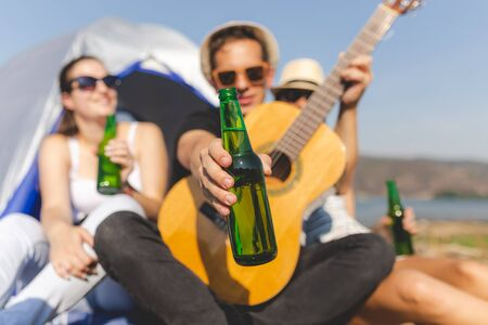 Close up of young man with acoustic guitar holding beer bottle while sitting with his friends in front of tent in nature. Camping and freedom concept. Banco de Imagens